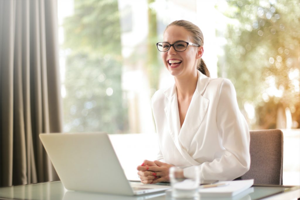 Professional working female smiling with laptop